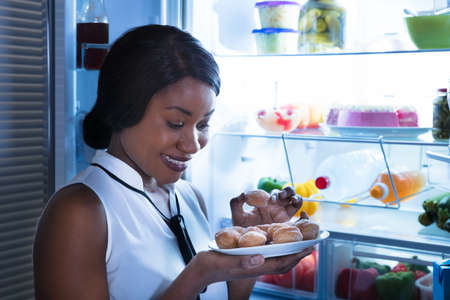 Close-up Of A Woman Eating Cookie Near Open Refrigerator Stock Photo