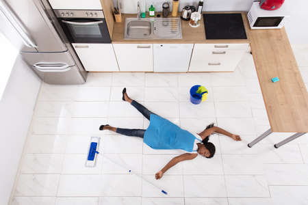 Unconscious African Housewife Lying On Floor With Bucket And Mop In Kitchen Stock Photo