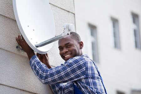 Jonge Afrikaanse man in uniforme montage TV satellietschotel op de muur