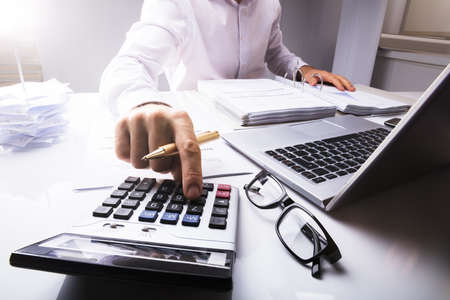 Mittelteil des Geschäftsmannes Steuer unter Verwendung des Taschenrechners mit Laptop auf Schreibtisch im Büro berechend Standard-Bild