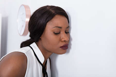 Close-up Of A Young African Woman Listening To Voice Coming From Wall