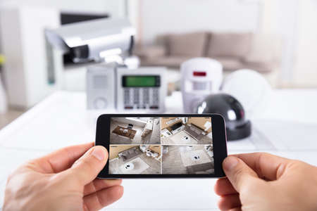 Close-up Of A Person's Hand Holding Mobile Phone With CCTV Camera Footage On Screen 写真素材