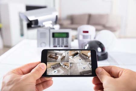 Primer plano de la mano de una persona sosteniendo un teléfono móvil con imágenes de cámara CCTV en pantalla Foto de archivo