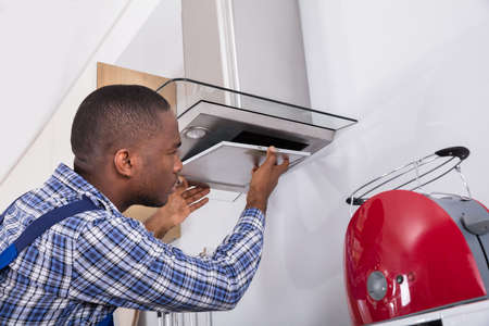 Young African Male Fixing Kitchen Extractor Filter In Kitchen Room
