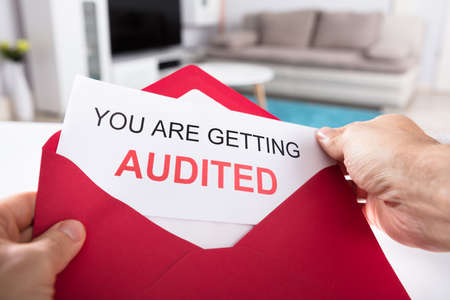 Close-up Of A Persons Hand Holding You Are Getting Audited Card In Red Envelope