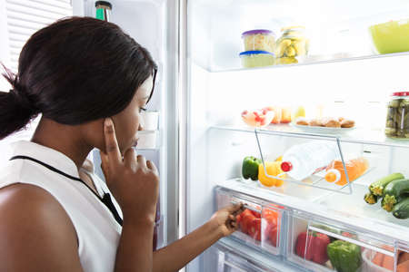 Young Woman Looking In Fridge At Kitchen Foto de archivo