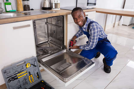 Young African Repairman Fixing Dishwasher In Kitchen 写真素材