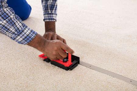 Ambachtsman die tapijt installeren op de vloer met behulp van monteur