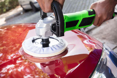 Close-up Of Person Hands Polishing Car With Orbital Polisher