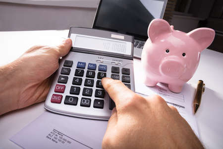 Businesspersons Hand Calculating Invoice With Calculator And Piggybank And On Desk In Office