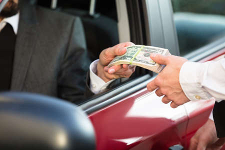 Businessman Sitting Inside Car Giving Bundle Of Banknote To Person