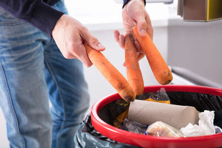 Close-up Of A Persons Hand Throwing Carrot In Dustbin