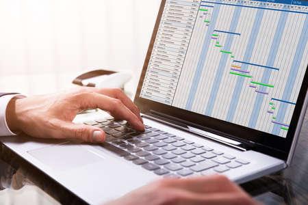 Primer plano de la mano del empresario que analiza la tabla de Gantt en la computadora portátil en el lugar de trabajo