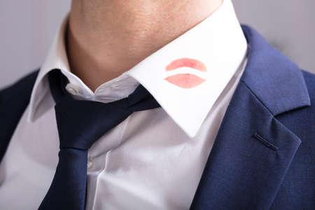 Primo piano di un uomo d'affari con i segni di bacio del rossetto sul colletto della camicia