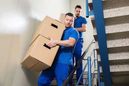 Twee Jonge Mannelijke Verhuizers in Blauwe Eenvormige Dragende Kartondozen op Trap