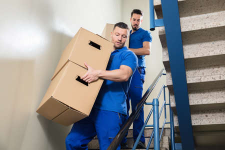 Two Young Male Movers In Blue Uniform Carrying Cardboard Boxes On Staircase