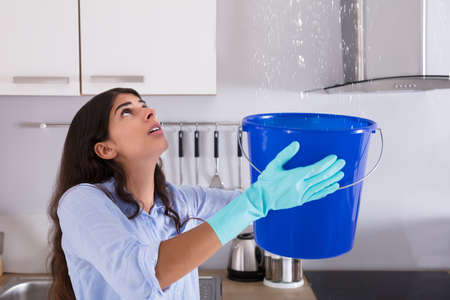 Worried Woman Holding Bucket While Water Droplets Leak From Ceiling In Kitchen Foto de archivo