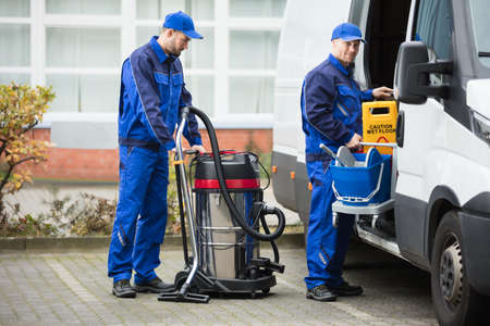 Two Young Male Janitor In Blue Uniform Unloading Cleaning Equipment From Vehicle