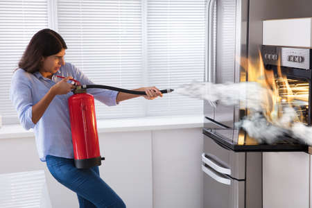 Young Woman Using Fire Extinguisher To Put Out Fire From Oven At Home