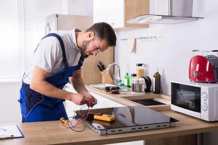 Mężczyzna technik naprawy kuchenki indukcyjnej z multimetrem cyfrowym w kuchni