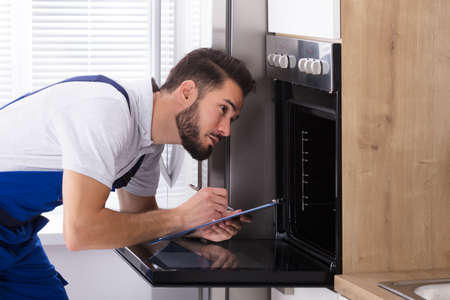 Young Male Electrician Writing On Clipboard While Looking At Oven In Kitchen Stock Photo