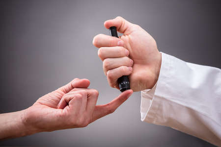 Close-up Of Doctors Hand Checking Patients Sugar Level With Glucometer On Grey Background