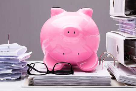 Close-up Of Upside Down Pink Piggy Bank On Documents With Eye Glasses On Desk