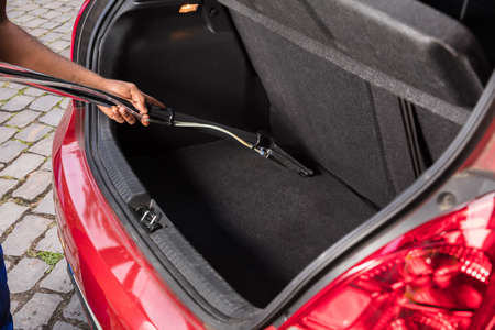 Close-up Of Handyman Vacuuming Car Trunk With Vacuum Cleaner