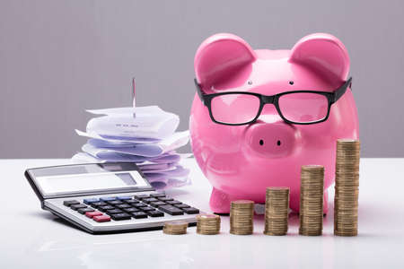 Close-up Of Stacked Coins With Piggy Bank And Calculator On Desk Archivio Fotografico