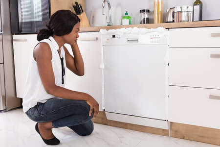 Sad African Woman Looking At Foam Coming Out From Dishwasher In Kitchen