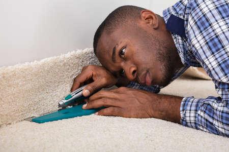 Close-up van een vakman montage tapijt op verdieping