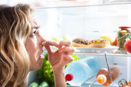 冷蔵庫の悪臭食品近く彼女の鼻を保持している若い女性をクローズ アップ 写真素材