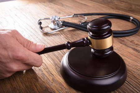 Close-up Of A Judge Hand Striking Gavel With Stethoscope On Wooden Desk In Courtroom