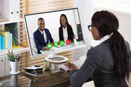 Joven empresaria africana Videoconferencia con sus colegas sonrientes en la computadora en el lugar de trabajo Foto de archivo