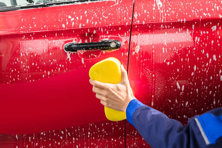 Close-up Of Workers Hand Washing Red Car With Yellow Sponge At Service Station Stock Photo