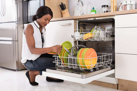 Smiling Young African Woman Arranging Plates In Dishwasher Stock Photo
