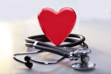 Primo piano di un cuore rosso con lo stetoscopio sullo scrittorio