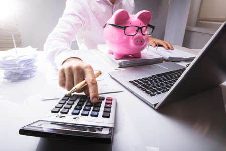 Midsection Of Businessman Calculating Tax Using Calculator With Piggybank And Laptop On Desk In Office Stock Photo