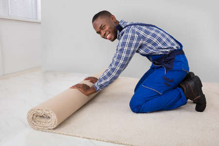 Young Male Handyman Rolling Carpet On Floor At Home Stockfoto