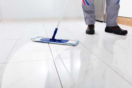 Worker Mopping Floor With Mop In Kitchen Zdjęcie Seryjne