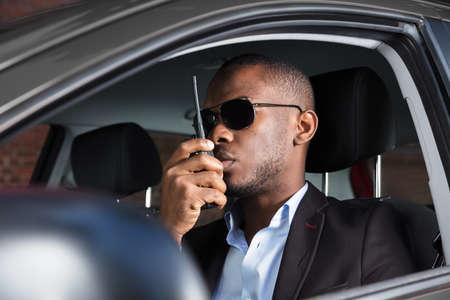 Surveillance Man With Sunglasses Sitting Inside Car Talking On Walkie Talkie Stock Photo