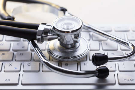 Close-up Of Medical Stethoscope On A Computer Keyboard At Desk