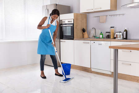 Happy African Housewife Cleaning Floor With Mop In Kitchen 写真素材