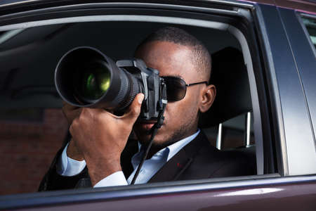 Private Detective Sitting Inside Car Photographing With SLR Camera Stock Photo