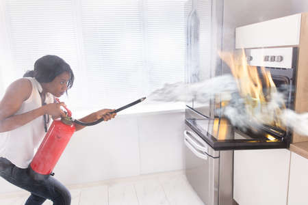 Young African Woman Using Fire Extinguisher To Stop Fire Coming From Oven In Kitchen Foto de archivo