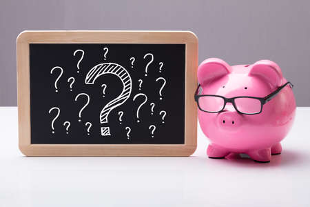 Close-up Of Piggy Bank With Eyeglass And Blackboard With Question Marks On Desk