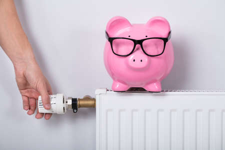 Close-up Of Man's Hand Adjusting Thermostat With Piggy Bank On Radiator Against Wall