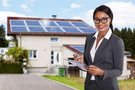 Portrait Of A Smiling African Businesswoman Filling Document In Front Of House