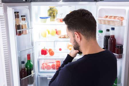 冷蔵庫で食べ物を見ている混乱した若者の背面図 写真素材 - 92388709