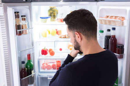 Rear View Of A Confused Young Man Looking At Food In Refrigerator Archivio Fotografico